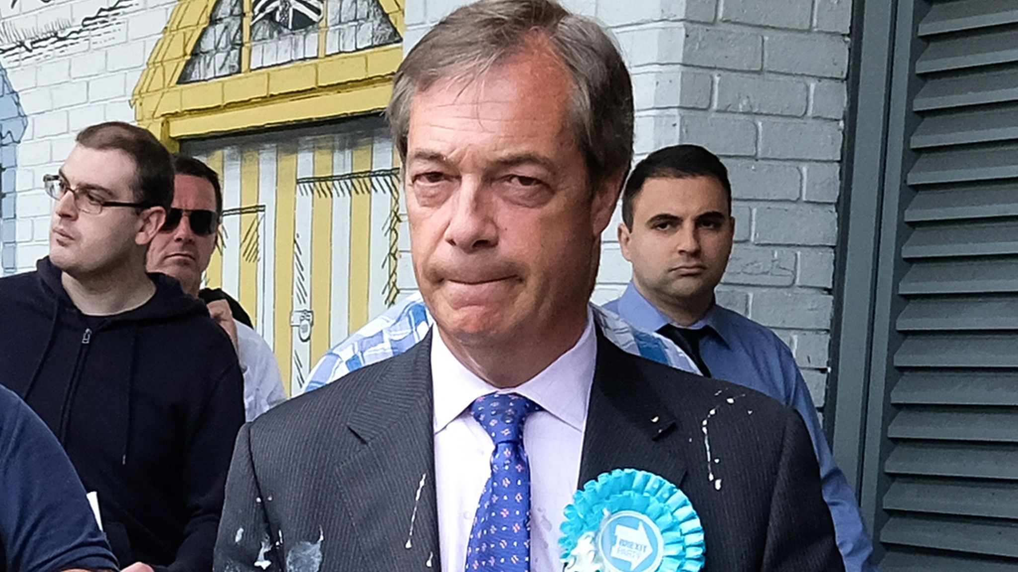 Nigel Farage is escorted to a car after having milkshake thrown over him