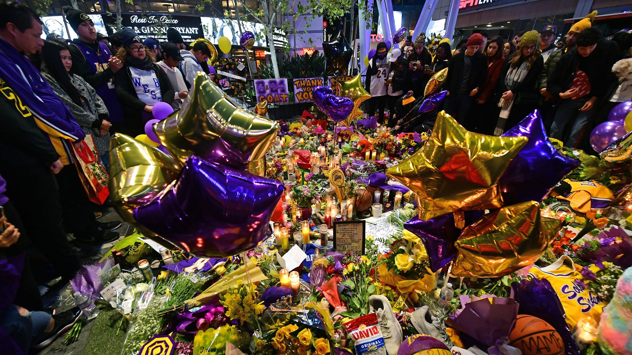 People gather in front of a makeshift memorial for former NBA and Los Angeles Lakers player Kobe Bryant and his daughter Gianna Bryant, who were killed with seven others in a helicopter crash on January 26, at LA Live plaza in front of Staples Center in Los Angeles on January 27, 2020. - Federal investigators sifted through the wreckage of the helicopter crash that killed basketball legend Kobe Bryant and eight other people, hoping to find clues to what caused the accident that stunned the world. (Photo by FREDERIC J. BROWN / AFP) (Photo by FREDERIC J. BROWN/AFP via Getty Images)