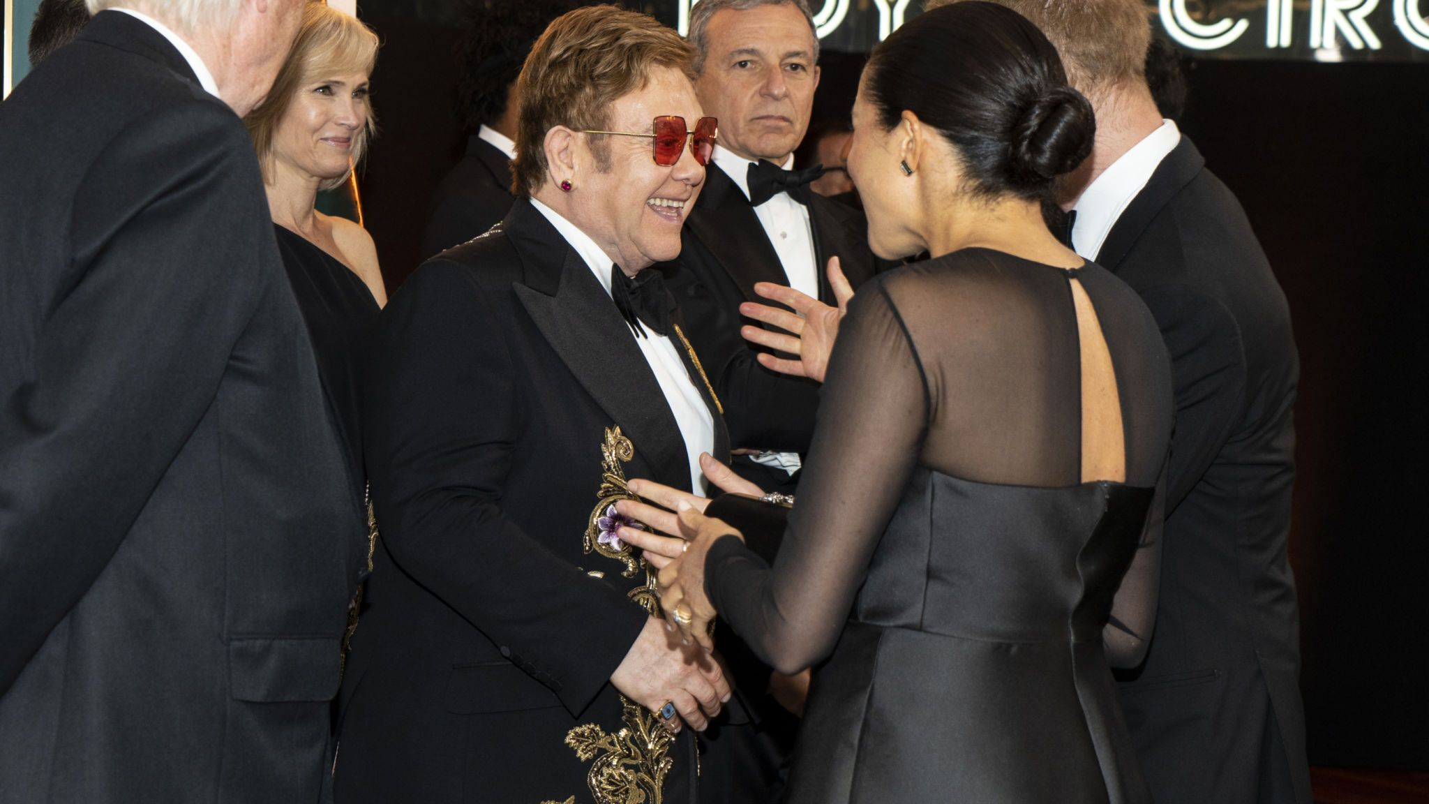 Prince Harry, Duke of Sussex and Meghan, Duchess of Sussex greet British singer-songwriter Elton John and David Furnish at the European Premiere of Disney's