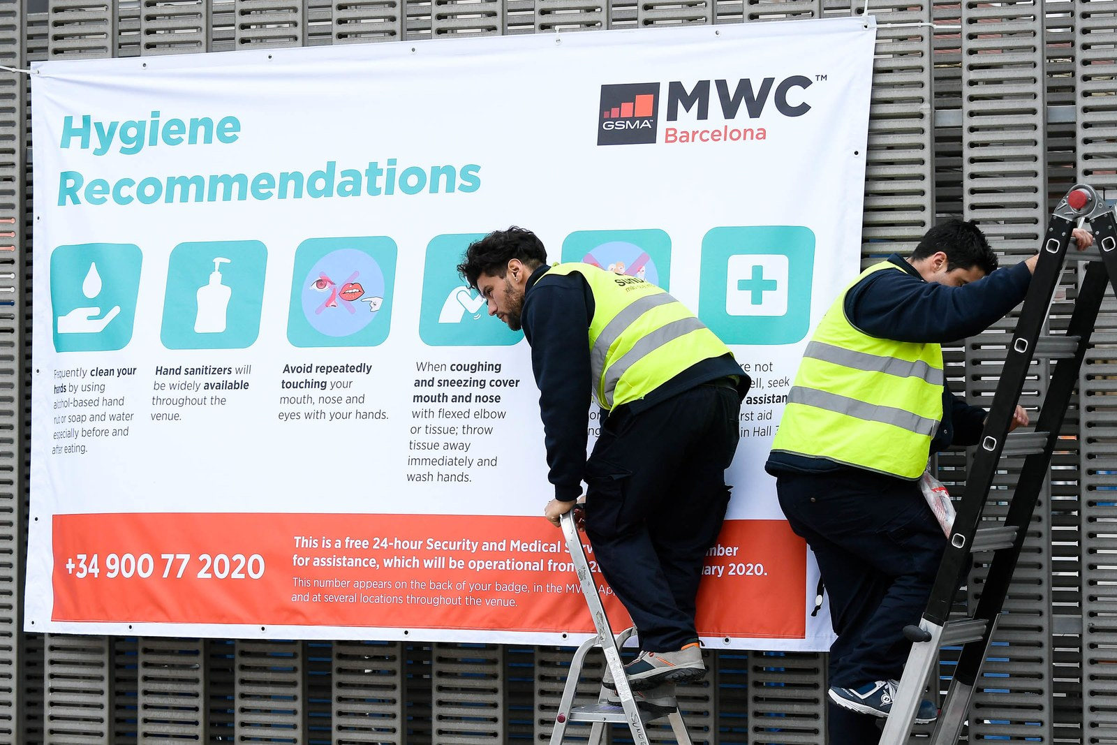 Workers on ladders install a banner with hygiene recommendations