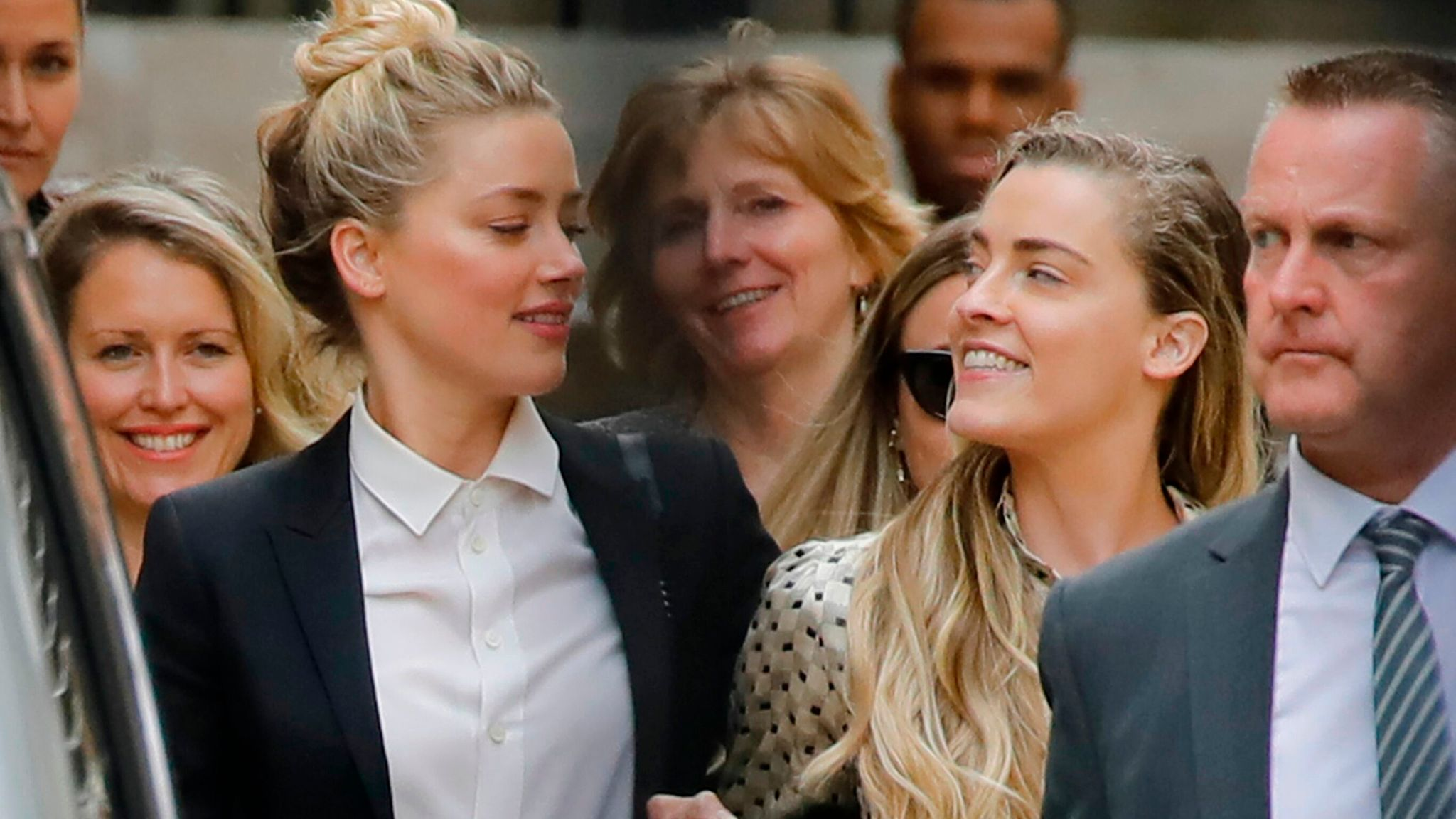 """US actress Amber Heard (L) leaves hand-in-hand with her sister Whitney Heard (R) from the High Court after a hearing in the libel trial by her former husband US actor Johnny Depp against News Group Newspapers (NGN) in London, on July 24, 2020. - Depp is suing the publishers of The Sun and the author of the article for the claims that called him a """"wife-beater"""" in April 2018. (Photo by Tolga AKMEN / AFP) (Photo by TOLGA AKMEN/AFP via Getty Images)"""