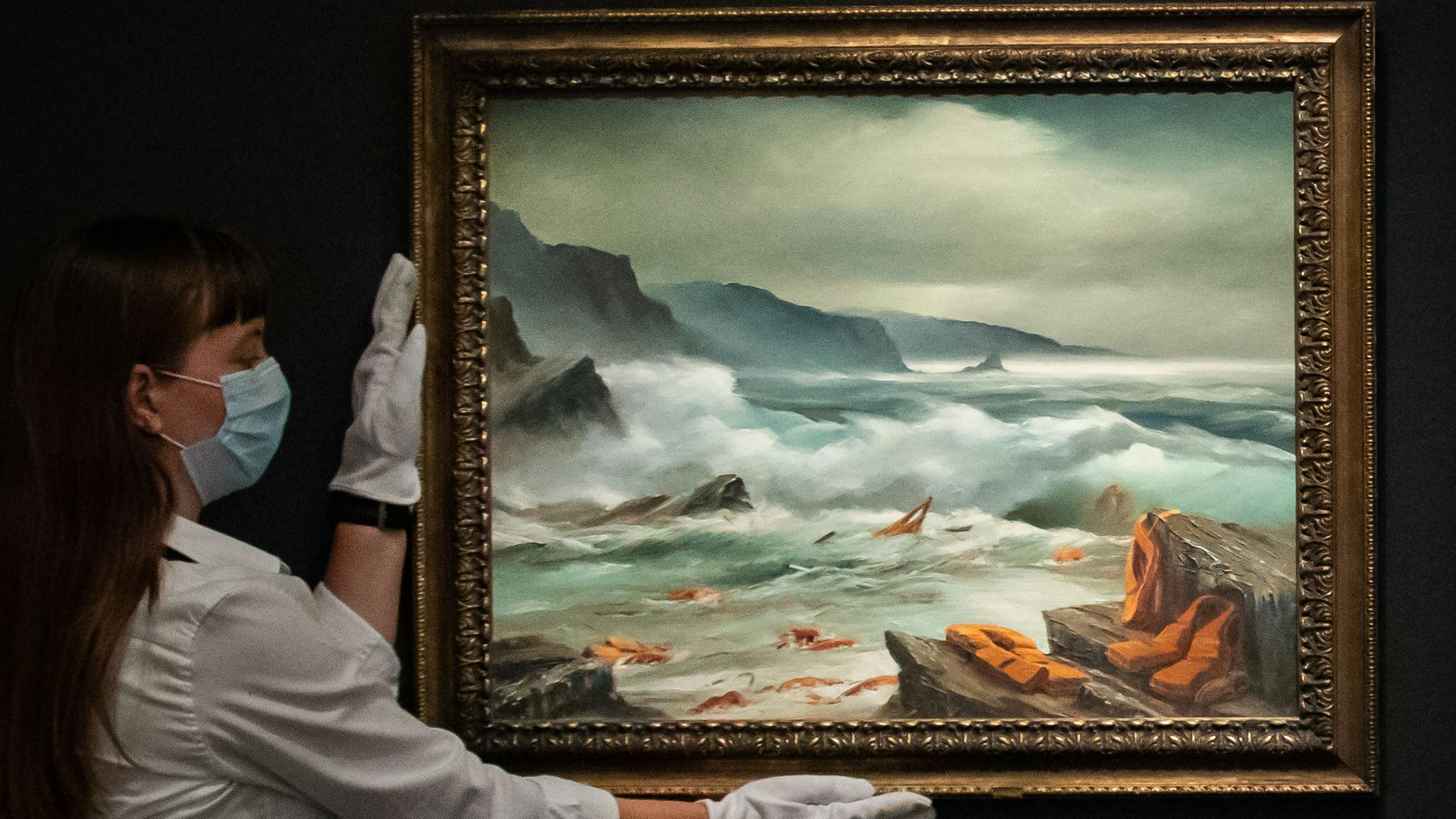 A gallery assistant holds one of a triptych titled Mediterranean Sea View 2017 by Banksy