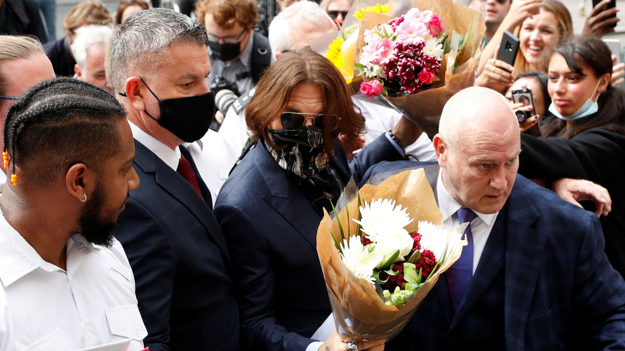 Johnny Depp is given flowers as he arrives at the High Court on 24 July
