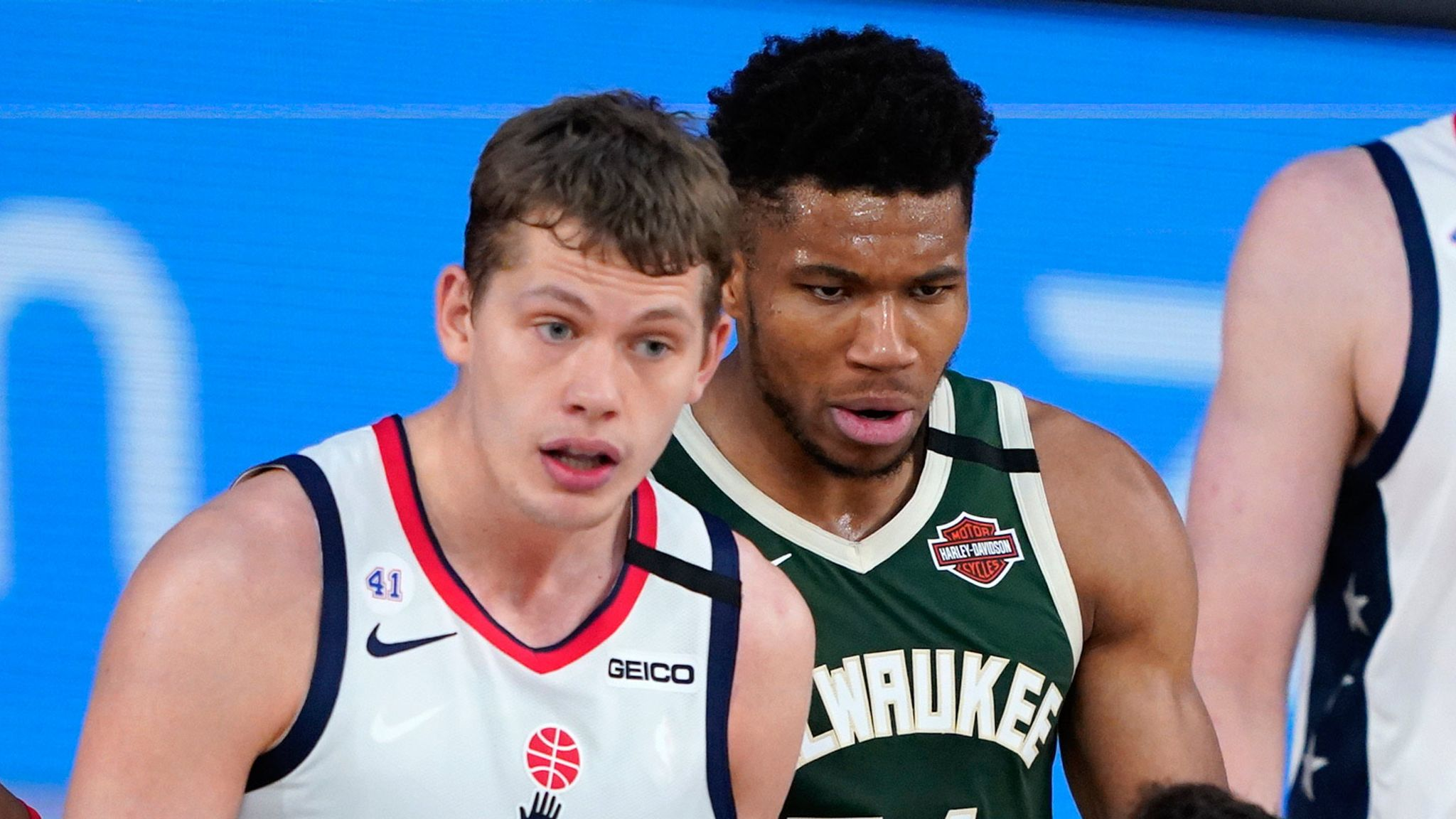 Mo Wagner and Giannis Antetokounmpo are reprimanded by the referee