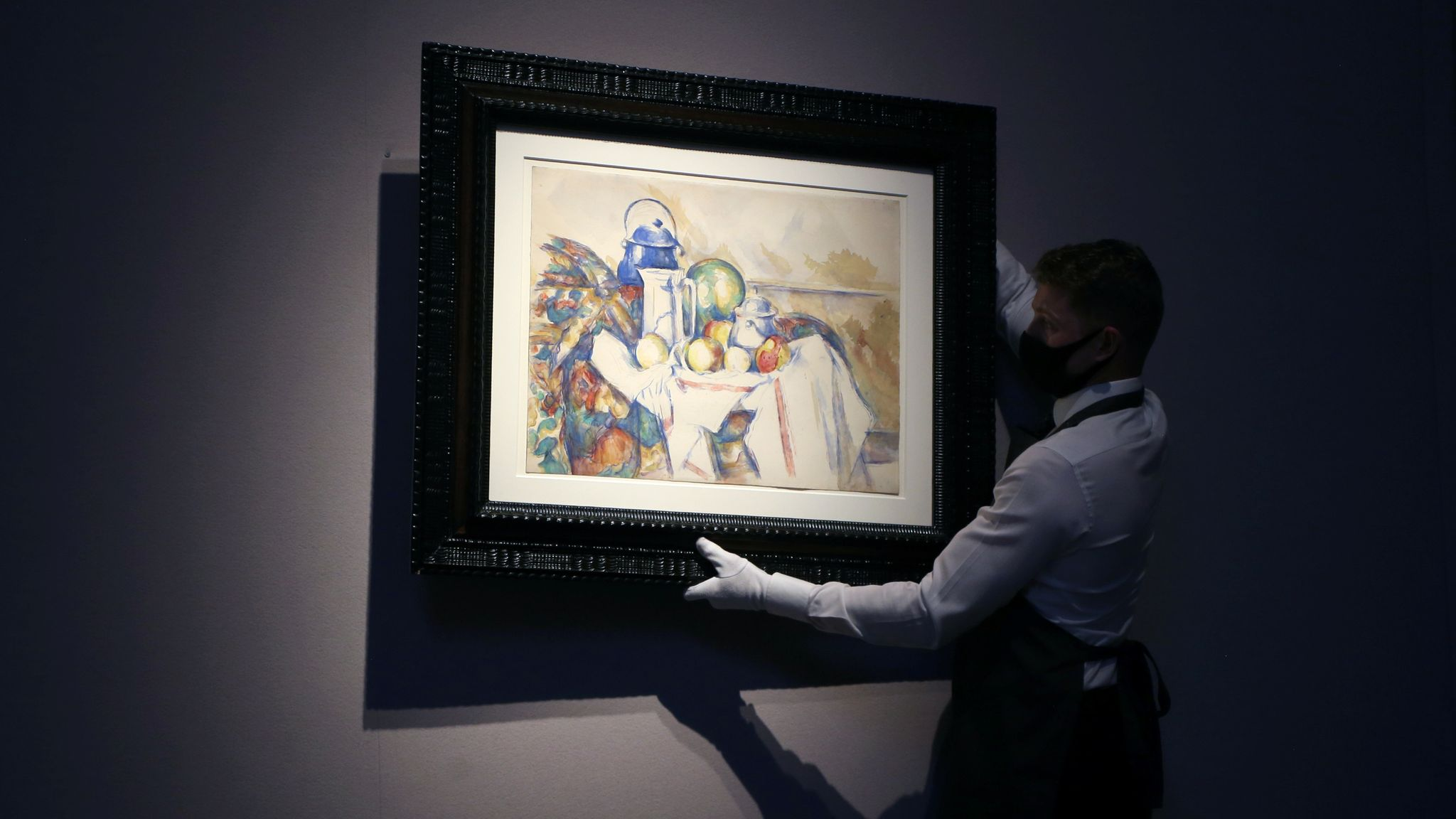 An employee holds a work by Paul Cezanne at Christie's auction house in London, Britain September 9, 2020. REUTERS/Tom Jacobs