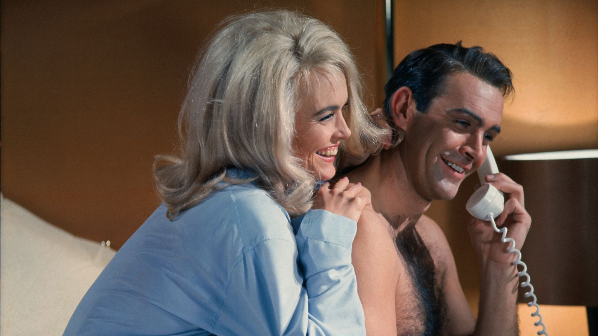 Sean Connery and Jill Masterson (Original Caption) James Bond (Sean Connery) and Jill Masterson (Shirley Eaton) share a laugh on the phone in the James Bond flick, Goldfinger. 1964.