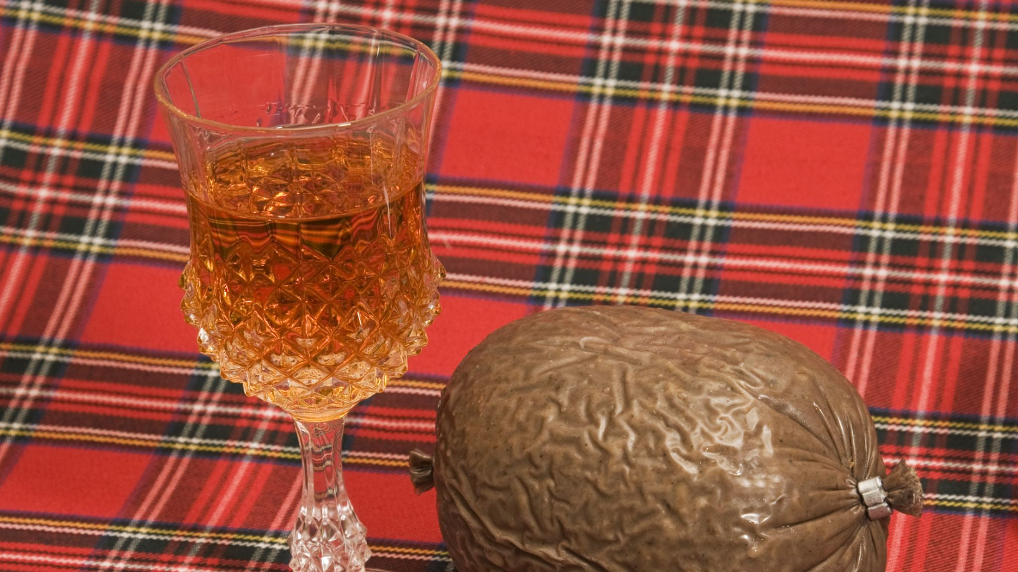 """""""Scotch whisky in a crystal thistle glass with a haggis on a tartan backdrop. Traditional Scottish fayre, particularly on Burns Night.Similar images from my portfolio:"""""""