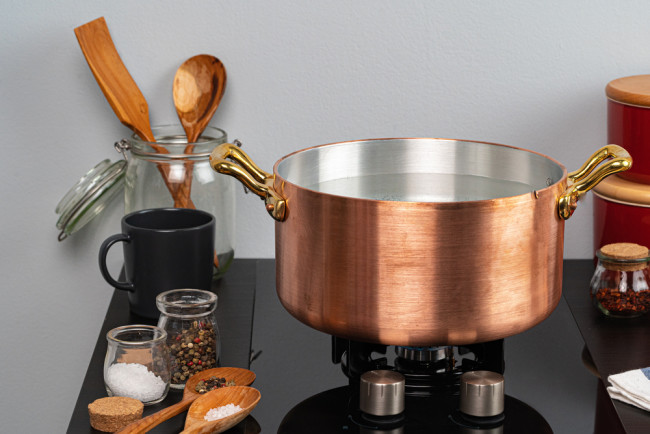 copper pan stovetop cooking - shutterstock 1703690812