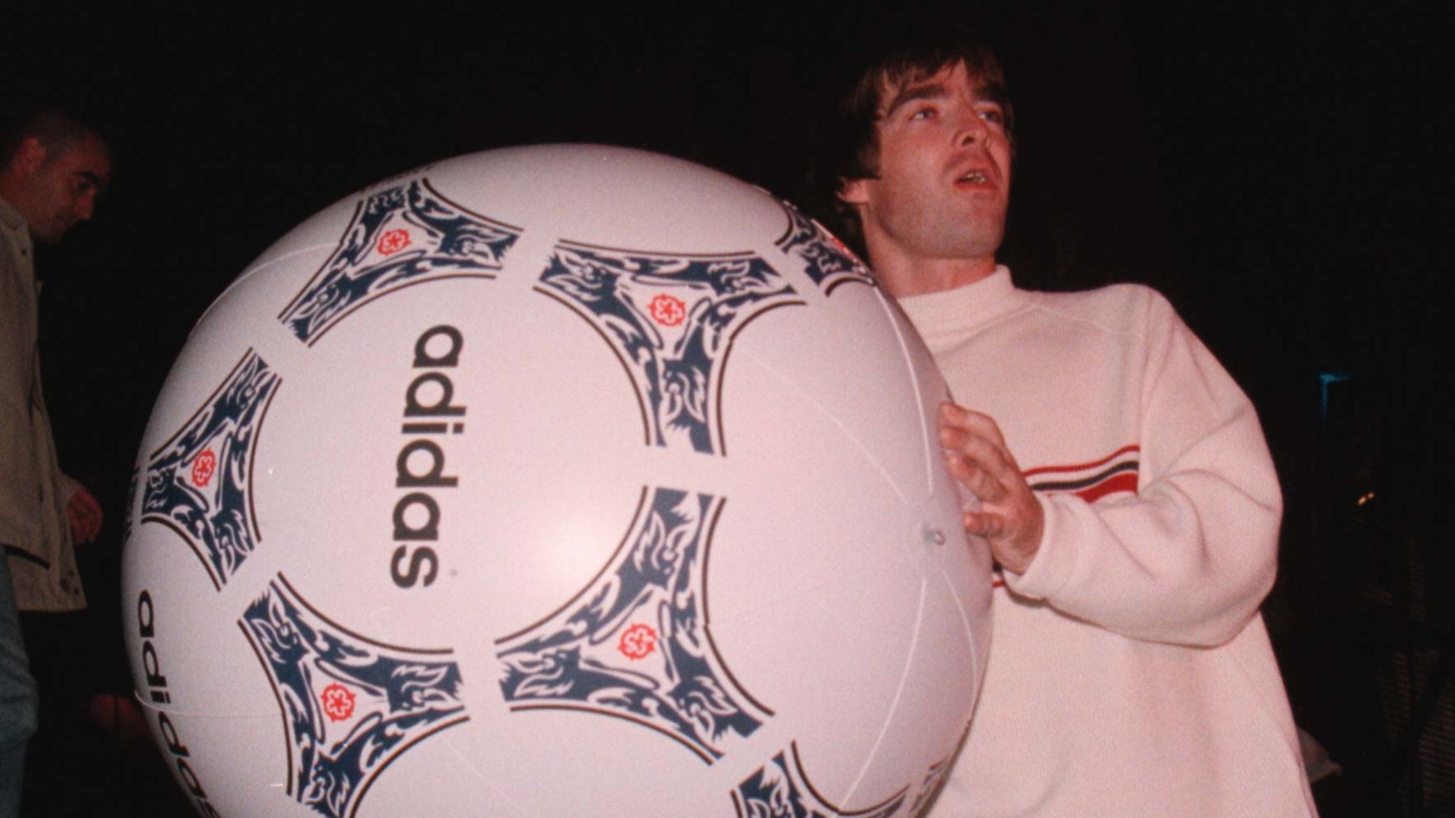 Noel Gallagher of Oasis throws a giant football into the audience during their concert at Knebworth Park in Hertfordshire in August 1996